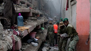 Kenyan National Youth Service personnel remove stones with hands at the site of a building collapse