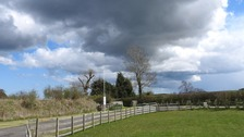 dark clouds and blue sky over field and road