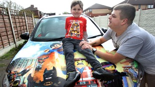Parents with autistic son paint car with Lego characters