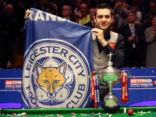 Mark Selby holds a Leicester City flag aloft after his victory.
