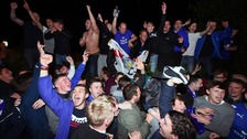 Leicester City fans celebrate outside Jamie Vardy's house after seeing their side crowned Barclays Premier League champions