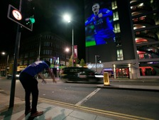 Leicester City fan bows down to a projection of Jamie Vardy