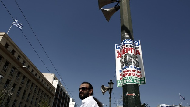 A man waits to cross a street in front of a banner calling for a 24-hour general strike against austerity measures in Athens, Greece.