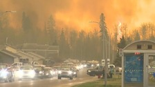 Evacuations and flights halted as Canada wildfire heads south