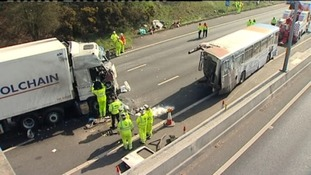 Recovery workers on site of crash between lorry and bus