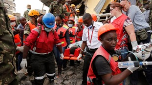 Emergency workers rescue a survivor from the collapsed building.