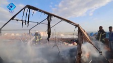 Smoke billows from the charred remains of one of the tents in the camp
