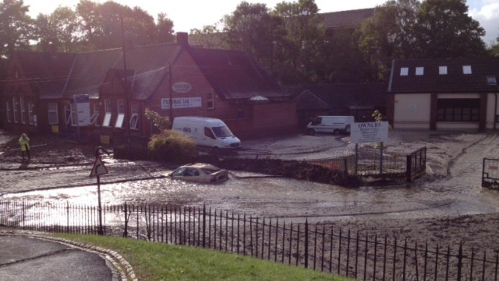 underground stream bursts through the road above in