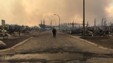 A Canadian mountie surveys the devastation in one area hit by the blaze