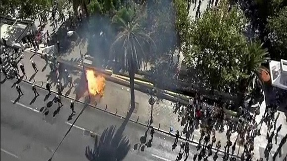 Riot police dodge petrol bombs from protesters in central Athens.