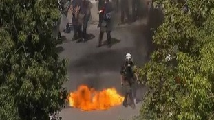 A police officer pictured avoiding a petrol bomb.
