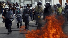 A molotov cocktail explodes beside riot police officers near Syntagma square during a 24-hour labour strike in Athens.