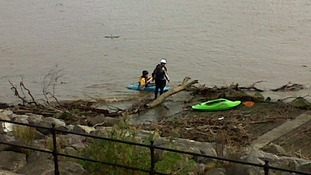 Kayakers struggle to get past debris