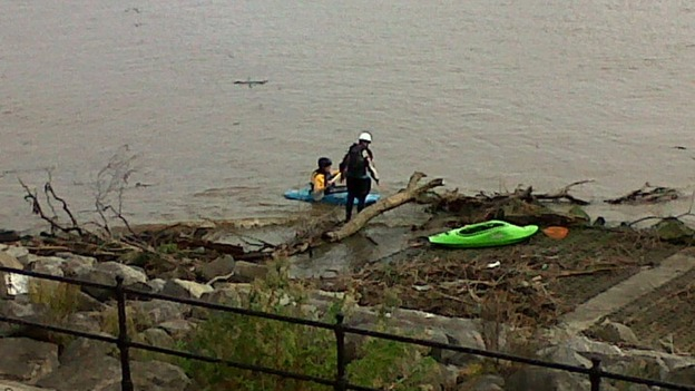Kayakers struggle to get past debris