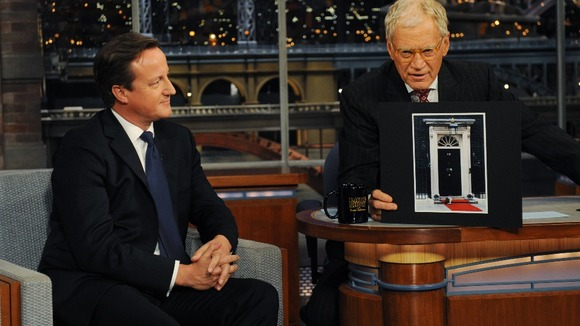 David Cameron looks on as David Letterman, holds up a picture of Larry the cat outside 10 Downing Street