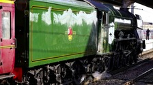 he Flying Scotsman, painted in its traditional colours, passes through Peterborough railway station