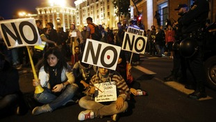 Protesters take part in a sit-in during a demonstration outside Madrid's Parliament