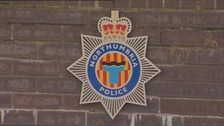 Northumbria Police force badge on a brick wall