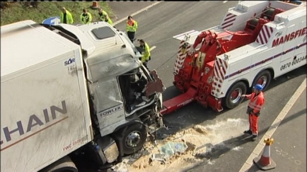 Workers attempting to tow away the lorry from the crash scene