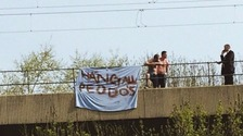 shirtless protestors on bridge.