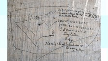 drawing on a wall of a bull's head and some words