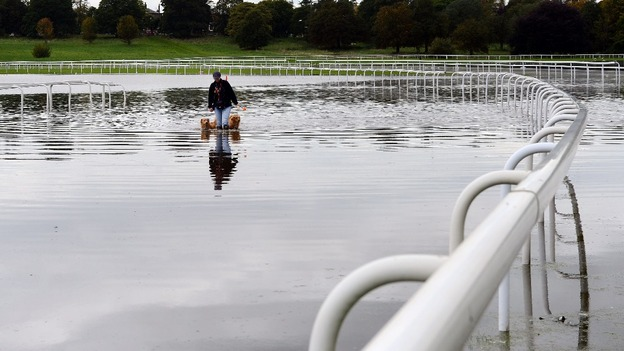 A dog walker on the York Racecourse walks through flood water