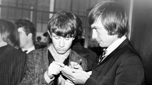 The Rolling Stones's Charlie Watts signing an autograph for a young fan, at Dublin Airport