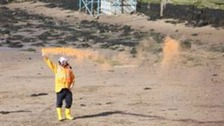 A Whitby RNLI volunteer crew member holds a flare to help the air ambulance land