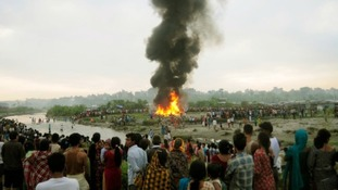 People watch the burning wreckage.