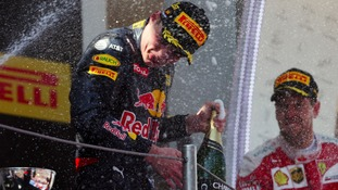 Verstappen is drenched in champagne on the podium.