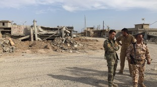 Peshmerga fighters in Basheer stand in front of destroyed buildings
