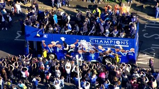 Four open top buses are carrying the Premier League champions