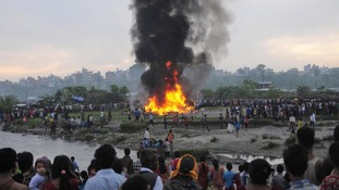 Nepalese gather around the burning wreckage at the crash