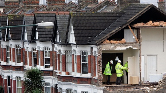 Assessors look at damage to a property on Chamberlayne Road in the Kensal Rise area of north London the day after a small tornado struck.