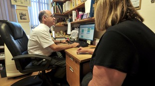 A doctor speaks with a patient in his practice room