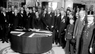Sir Edward is seen signing the Ulster Covenant at Belfast City Hall, Ulster.