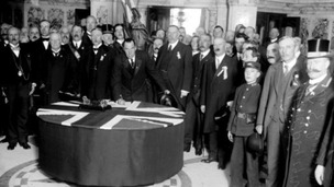 Sir Edward Carson is seen signing the Ulster Covenant at Belfast City Hall in 1912.