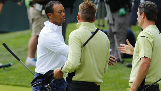 Tiger Woods shakes hands with Team Europe golfers Rose and Poulter after Team Europe won their match