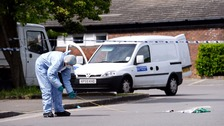 A forensic officer examines the scene at a car park in Hampton.