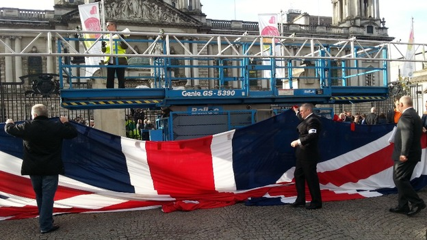 The gigantic Union Flag is hoisted by members of the Orange Order