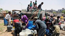 Local residents fill their empty containers with water from municipal tanker on a hot summer day in Ahmedabad