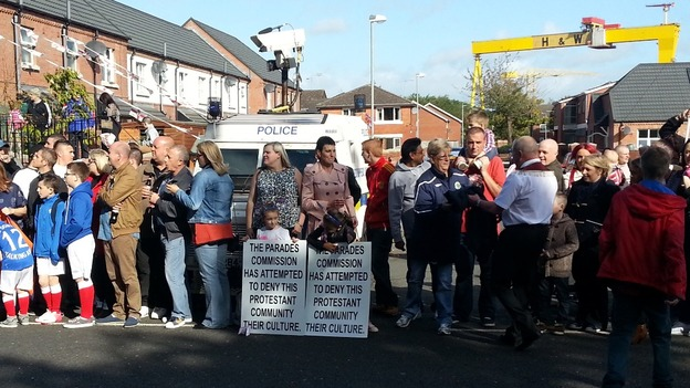 Residents of East Belfast wait for the parade to pass, in the shadow of the iconic Harland and Wolff cranes.