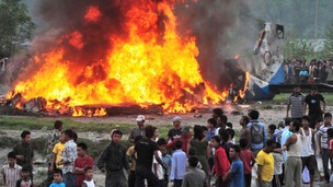 Nepalese gather around the burning wreckage at the crash site of a Sita Air airplane near Katmandu, Nepal
