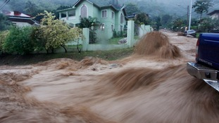 A torrent of water water rushes past a vehicle at Westvale Park, Glencoe, about 10 km (6 miles) from the capital Port-of-Spain