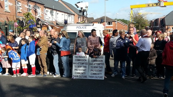 Residents of East Belfast wait for the parade to pass, in the shadow of the iconic Harland and Wolff cranes