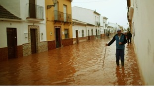 A man wades through floodwaters in Bobadilla, near Malaga.