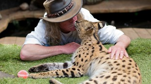 Iain Newby and his serval cat Squeaks at home in Great Wakering, Essex