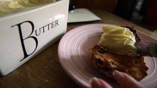 Butter is spread on a hot cross bun