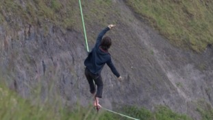 Pair attempt perilous cliff crossing on inch-thick slackline