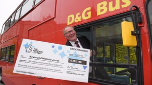 Mr Jones with a cheque for £6.1 million at the wheel of a bus